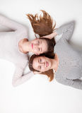 Retrato das irmãs felizes que encontram-se no assoalho Foto de Stock