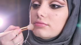 Retrato das mãos fêmeas que fazem a composição e que põem o highlighter para a mulher muçulmana nova no hijab sobre luzes brilhan video estoque