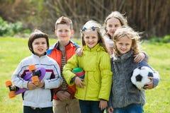 Retrato das meninas e dos meninos que jogam no campo Imagens de Stock
