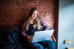 Retrato das mulheres de negócios bonitas novas que apreciam o café durante o trabalho no laptop portátil, utilização encantador d Imagens de Stock Royalty Free