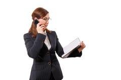 Retrato das orelhas bonitas de uma mulher de negócios 50 velhas com o telefone celular isolado no branco Imagem de Stock Royalty Free