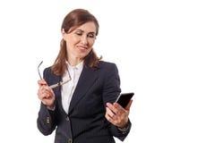 Retrato das orelhas bonitas de uma mulher de negócios 50 velhas com o telefone celular isolado no branco Imagens de Stock