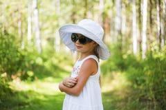 Retrato de óculos de sol vestindo de uma menina bonito e de um chapéu em uma floresta ensolarada do verão Imagem de Stock Royalty Free
