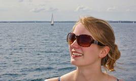Retrato de óculos de sol vestindo de uma jovem mulher bonita com o mar e um veleiro distante no fundo foto de stock