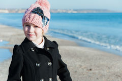 Retrato de 8 años de la muchacha cerca del mar en la estación rosada del frío del sombrero Imagen de archivo libre de regalías