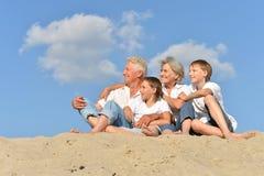 Retrato de abuelos con sus nietos en la arena imagenes de archivo