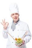 Retrato de admirar o cozinheiro chefe com salada nas mãos que mostram a mão foto de stock