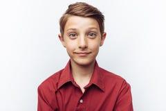 Retrato de adolescente lindo sonriente en el fondo blanco, en camisa roja, anuncio, parte movible del texto Fotos de archivo