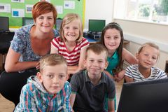 Retrato de alumnos elementales en clase del ordenador con el profesor imagen de archivo