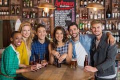 Retrato de amigos jovenes con las cervezas por la tabla en pub Fotos de archivo