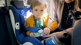 Retrato de 2 anos de bebê idoso que senta-se no assento da segurança do carro e que guarda um brinquedo Fotos de Stock Royalty Free