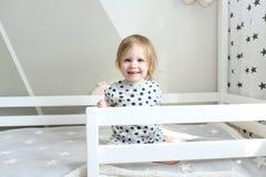 Retrato de 2 anos bonitos da menina em sua cama em casa Fotos de Stock Royalty Free