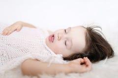Retrato de 2 anos de criança que dorme na manta branca da pele Fotografia de Stock