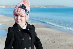 Retrato de 8 anos de menina idosa perto do mar na estação cor-de-rosa do frio do chapéu Imagem de Stock Royalty Free