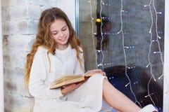 Retrato de 10 anos de livro de leitura velho da criança na janela no Natal Imagem de Stock