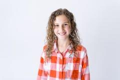 Retrato de 9 anos de menina idosa com cabelo encaracolado, no cinza Fotografia de Stock