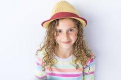 Retrato de 9 anos de menina idosa com cabelo encaracolado, no cinza Fotos de Stock Royalty Free