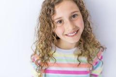 Retrato de 9 anos de menina idosa com cabelo encaracolado, no cinza Imagens de Stock