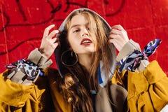Retrato de apelar o modelo elegante da foto que levanta o hoodie cinzento vestindo imagem de stock