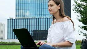Retrato de aproximação de uma jovem sentada na grama e usa laptop, empresária digitando no teclado, negócios modernos vídeos de arquivo