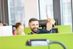 Retrato de auriculares vestindo do homem de negócios adulto meados de feliz ao gesticular os polegares acima no escritório imagem de stock