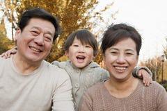 Retrato de avós e do neto felizes no parque no outono Imagens de Stock