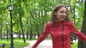 Retrato de bailar a la mujer joven en chaqueta de cuero roja en el parque verde metrajes