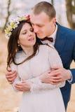 Retrato de boda del abarcamiento elegante de novia y del novio del recién casado feliz al aire libre con los árboles deshojados e Fotografía de archivo libre de regalías