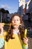 Retrato de bolhas de sabão de sopro da moça à moda na rua Imagens de Stock Royalty Free