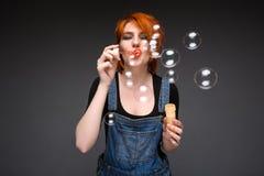 Retrato de bolhas de sopro da moça sobre o fundo cinzento Imagens de Stock