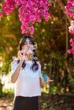 Retrato de bolhas de sab?o de sopro da jovem mulher no fundo cor-de-rosa das flores na praia foto de stock royalty free