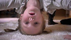 Retrato de cabeça para baixo do close-up da menina caucasiano pequena que faz uma ponte e que mostra as caras engraçadas na câmer filme