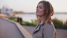 Retrato de caminhadas felizes da menina no lago e de voltas na câmera filme