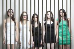Retrato de cinco jovens mulheres que estão de lado a lado barras da prisão dos behinds imagens de stock royalty free