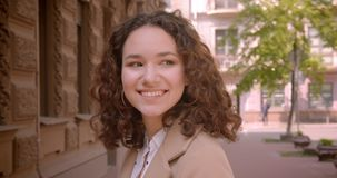 Retrato de close-up de uma jovem estudante de cabelos longos e curvada, sorrindo alegremente para uma câmera ao ar livre filme