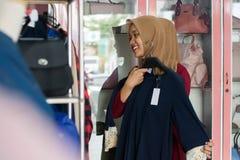 Retrato de compras musulmanes de la mujer del asi?tico joven atractivo en un strore de la moda foto de archivo libre de regalías