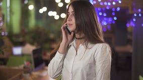 Retrato de confiado en el desgaste formal de la blusa blanca que habla por el teléfono móvil de la célula en oficina o café moder almacen de video