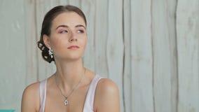Retrato de consideravelmente, jovem mulher com composição bonita e penteado elegante filme