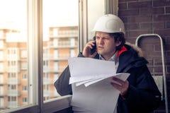 Retrato de construtor não barbeado interessado que diz pelo móbil ao manter projetos diferentes disponivéis Uma comunicação e fotografia de stock