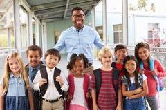 Retrato de crianças e de professor da escola primária no corredor imagens de stock royalty free