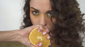 Retrato de criar a la muchacha hermosa de los ojos que sostiene una naranja cerca de sus labios y que exprime creando el jugo que almacen de video