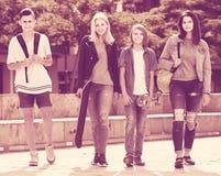 Retrato de cuatro adolescentes que caminan junto en ciudad el verano DA Fotos de archivo
