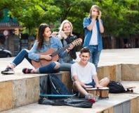 Retrato de cuatro adolescentes que juegan la música junta al aire libre Foto de archivo