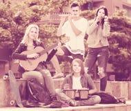 Retrato de cuatro adolescentes que juegan la música junta al aire libre Fotografía de archivo