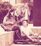 Retrato de cuatro adolescentes que juegan la música junta al aire libre Foto de archivo libre de regalías