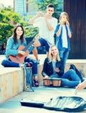 Retrato de cuatro adolescentes que juegan la música junta al aire libre Imágenes de archivo libres de regalías