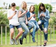 Retrato de cuatro adolescentes que se sientan con su outd de los teléfonos móviles Fotos de archivo libres de regalías