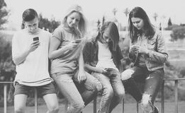 Retrato de cuatro adolescentes que se sientan con su outd de los teléfonos móviles Imágenes de archivo libres de regalías