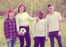 Retrato de cuatro amigos que presentan en campo del campo con la bola Fotos de archivo libres de regalías