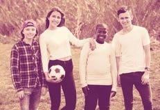 Retrato de cuatro amigos que presentan en campo del campo con la bola Imagenes de archivo